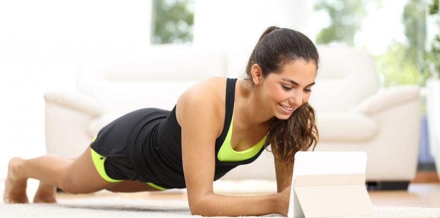 Fitness woman exercising on the floor at home and watching fitness videos in a tablet