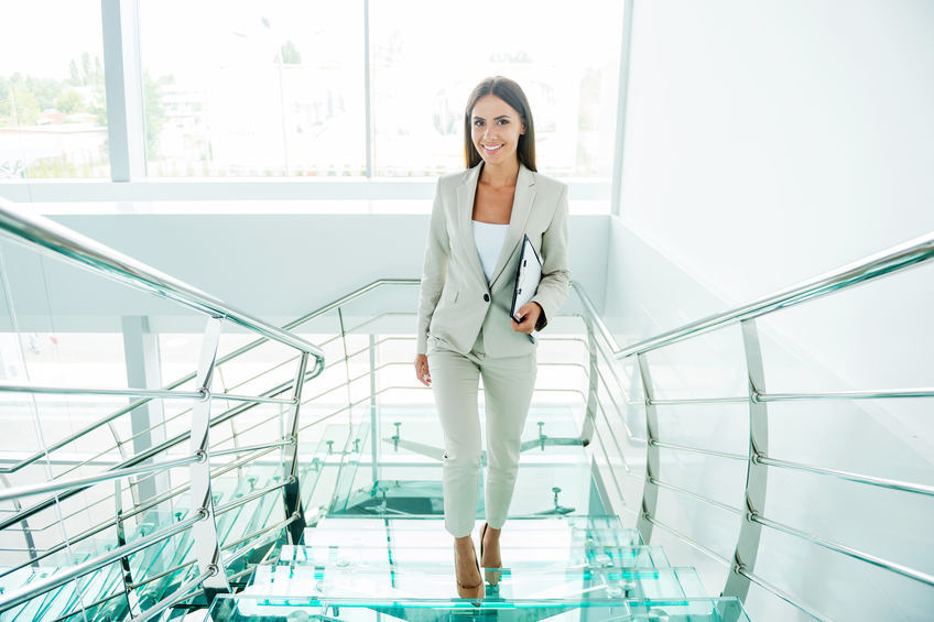 Beautiful young businesswoman in formalwear moving up by staircase and smiling