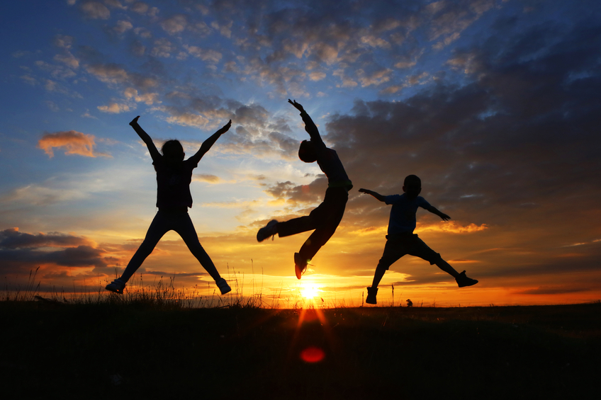 Three friends jumping at sunset, freedom concept.