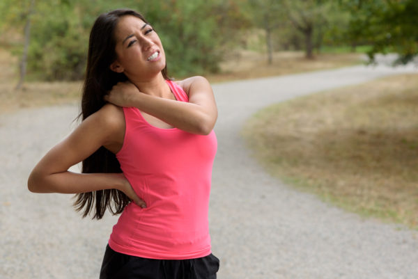 Young woman out jogging suffers a muscle injury standing holding her neck and lower back while grimacing in pain on a rural road, close up upper body view