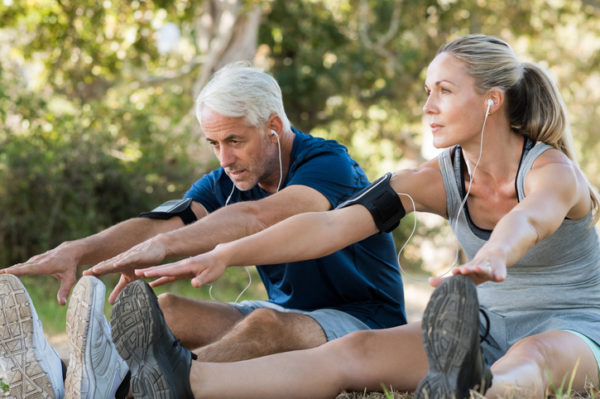 Mature couple stretching at park and listening to music. Athletic senior couple exercising together outdoor. Fit senior runners stretching before running outdoors.
