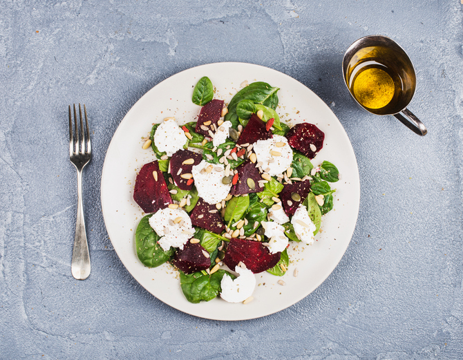 Salad with roasted beetroot, spinach, soft goat heese and seeds in light plate over grey concrete textured background, oil in saucer. Top view