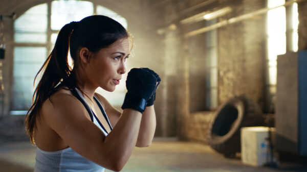 Beautiful Athletic Woman holds her Arms Ready for Defending Herself. It is a Part of Her Intensive Cross Fitness Gym Training.