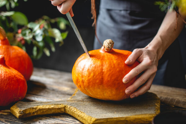 A woman chef cleans an orange pumpkin to prepare for baking. Concept autumn food in a cozy dark wooden kitchen with yellow flowers